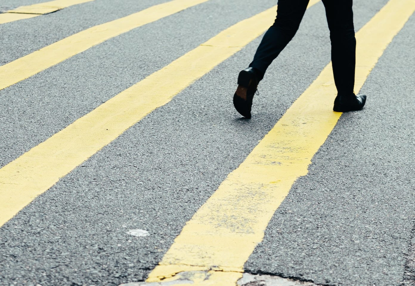 person walking on street with yellow lines
